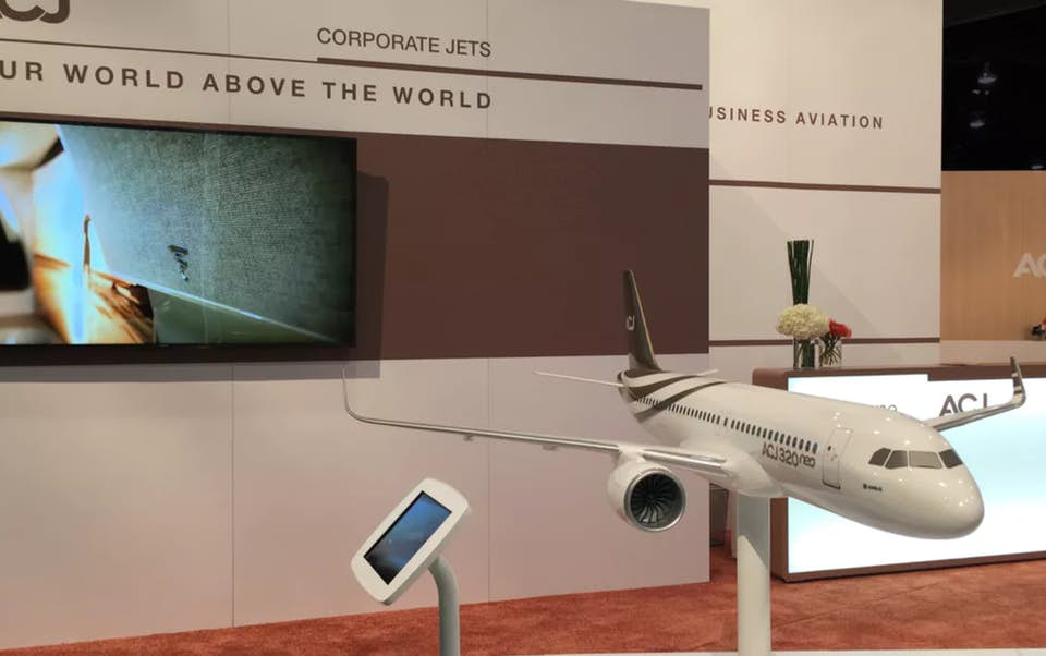 Airbus interactive kiosk beside a display model at a trade show.