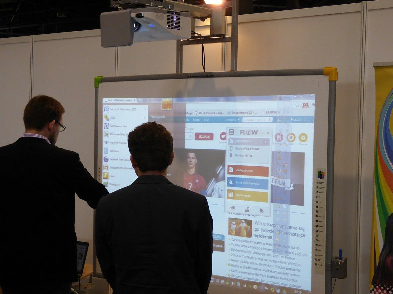 Man viewing interactive whiteboard at trade show exhibit.