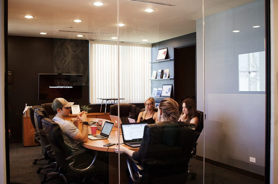 Marketing team researching competitors in conference room.